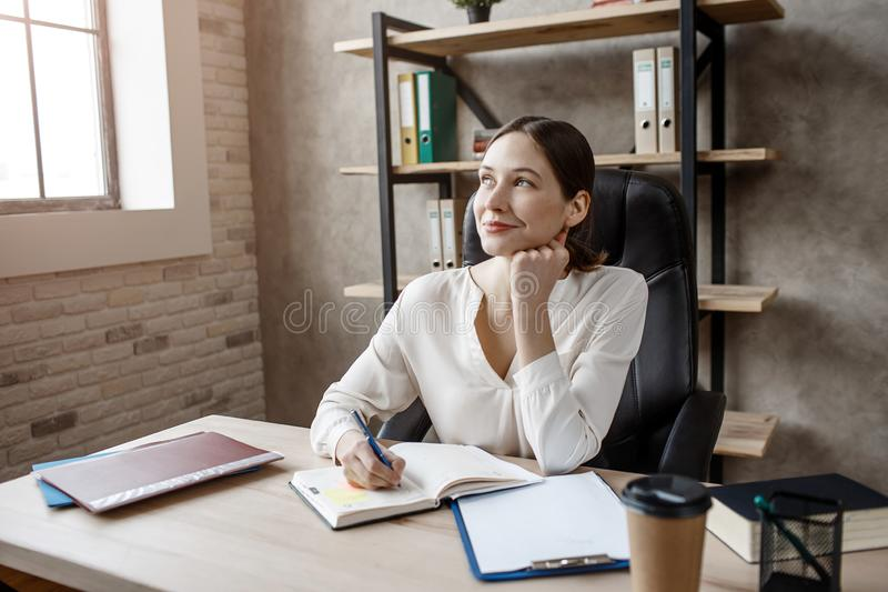 Young businesswoman sit at table in room. She write in notebook and smile. royalty free stock photography