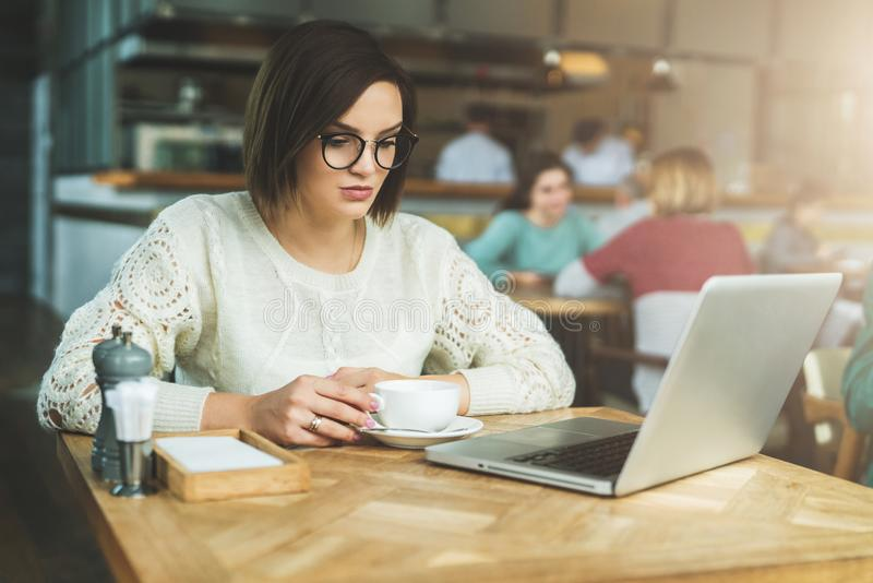 Young businesswoman sitting in cafe at table,drinking coffee and working on laptop.Student is studying online. royalty free stock photo
