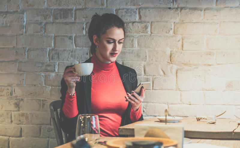 Young businesswoman sitting in cafe at wooden table, drinking coffee and using smartphone. royalty free stock photos