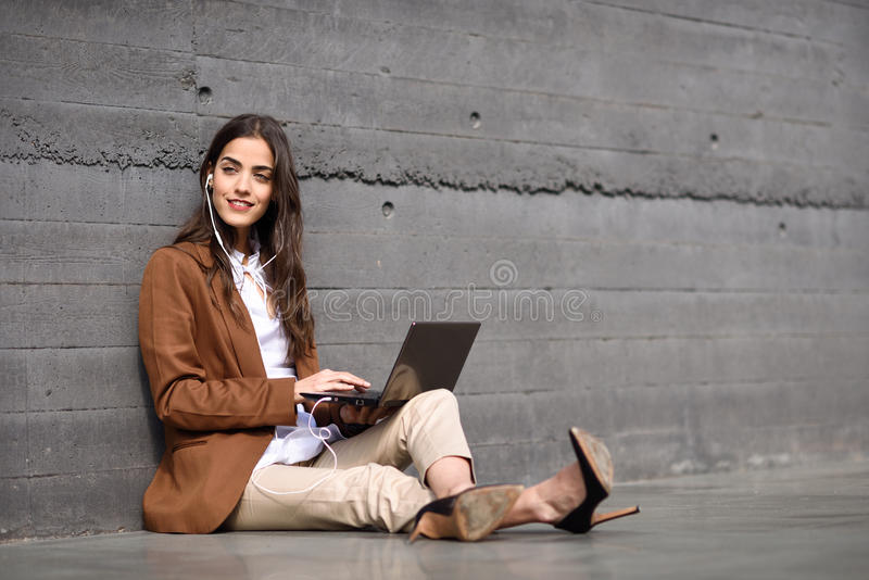 Young businesswoman sitting on floor looking at her laptop computer. royalty free stock images