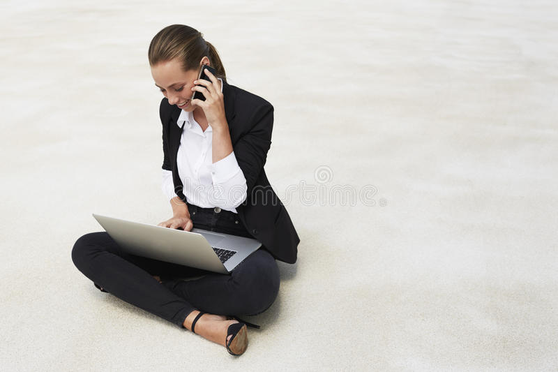 Young businesswoman sitting on floor stock images