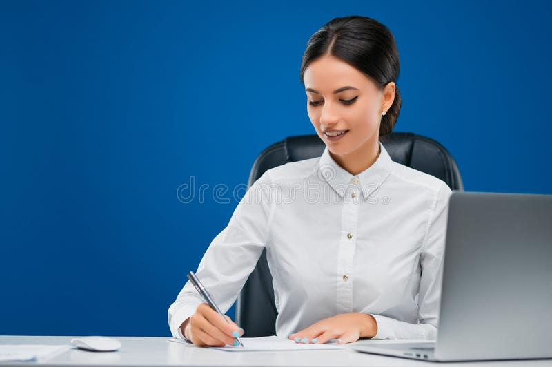 Young businesswoman sitting at her desk before a laptop happily writing new concepts on a sheet of paper, isolated on blue. Beautiful, young businesswoman royalty free stock photo