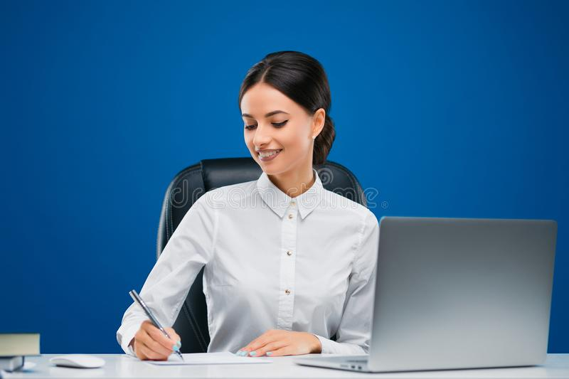 Young businesswoman sitting at her desk before a laptop proudly writing new concepts on a sheet of paper, isolated on blue. Beautiful, young businesswoman royalty free stock photography