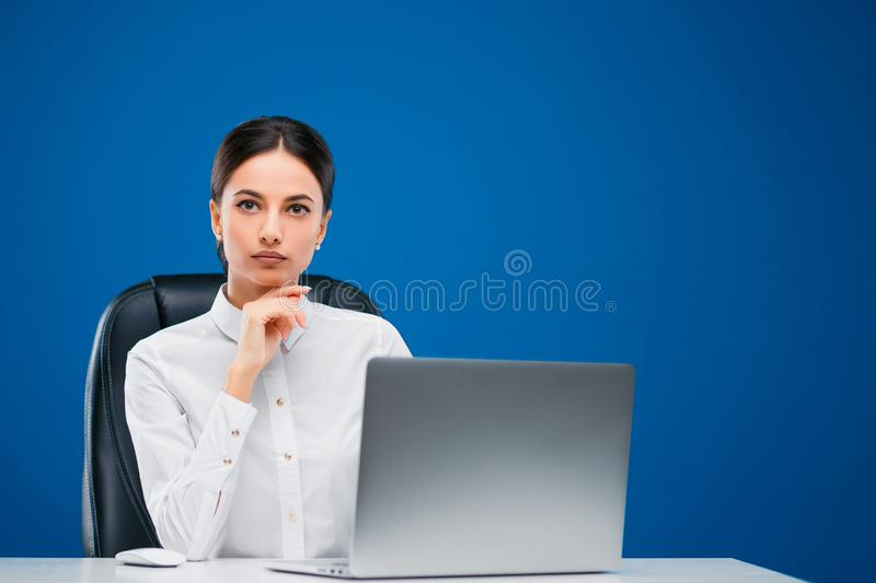 Young businesswoman sitting at her desk before a laptop thinking deeply about a new concept, isolated on blue background stock photography