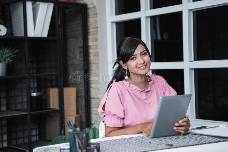 Young businesswoman sitting with her tablet in the office stock photo