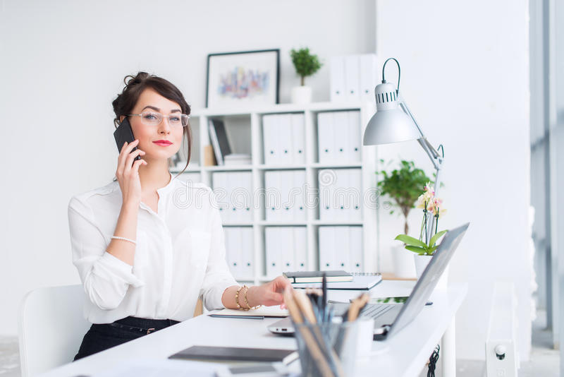 Young businesswoman sitting at her workplace, working out new business ideas, wearing formal suit and glasses, looking stock photos