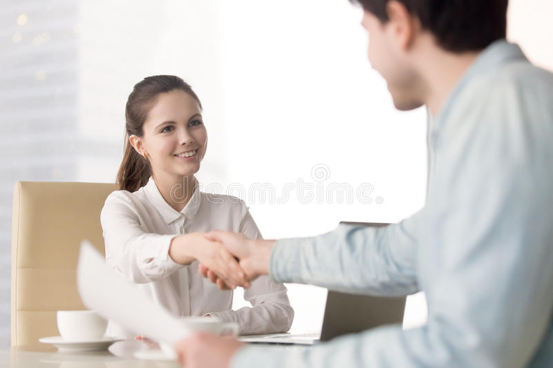 Young businesswoman sitting at office desk handshaking with stan stock photos