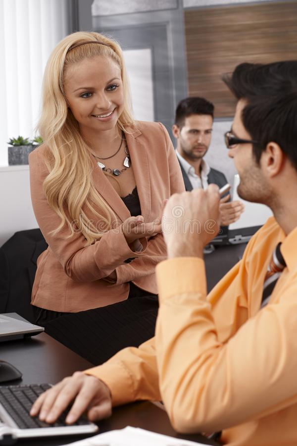 Young businesswoman talking to colleague stock photos
