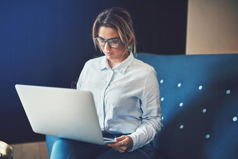 Young businesswoman sitting on a sofa working online stock photography