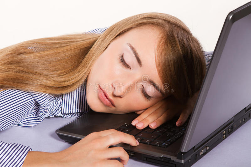 Young businesswoman sleeping on the laptop royalty free stock image