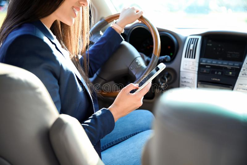 Businesswoman with smartphone on driver`s seat of car. Young businesswoman with smartphone on driver`s seat of car stock photos