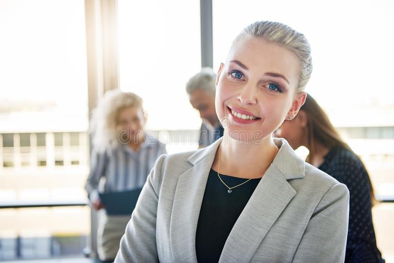 Young businesswoman smiling with colleagues talking in the background royalty free stock image