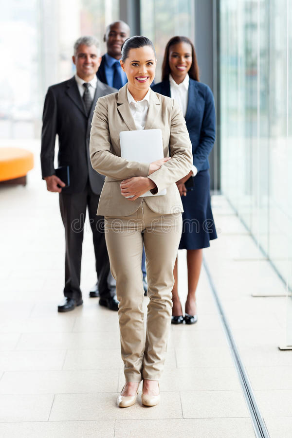 Young businesswoman standing in front of colleagues royalty free stock photo