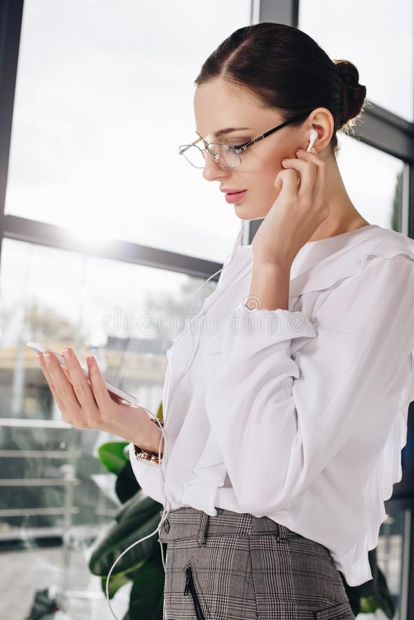 Young businesswoman standing in front of window, while listening to music in earbuds royalty free stock image