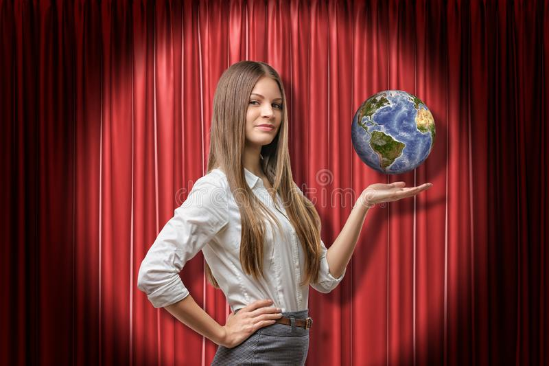 Young businesswoman standing in half-turn with hand on hip at red curtain lit up by spotlight and levitating small royalty free stock image