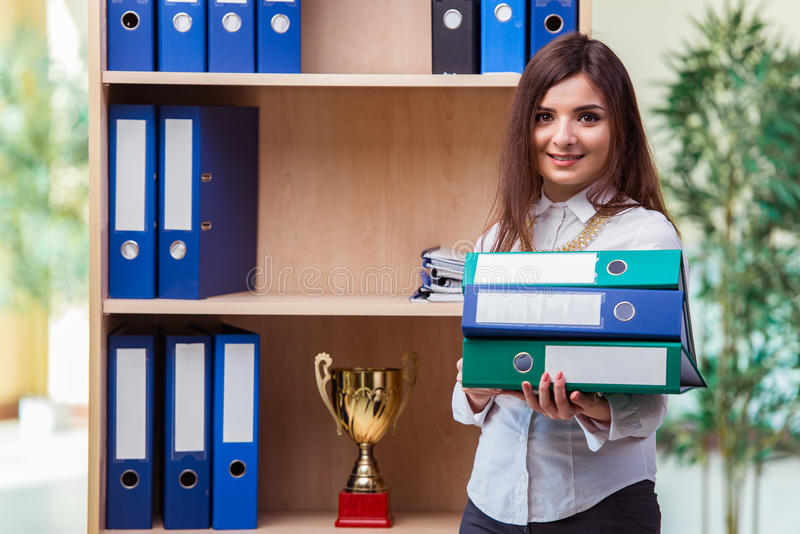 The young businesswoman standing next to shelf royalty free stock photos