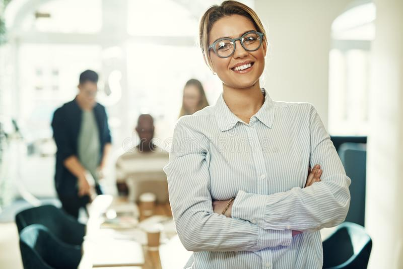 Young businesswoman standing in an office with colleagues behind royalty free stock photo