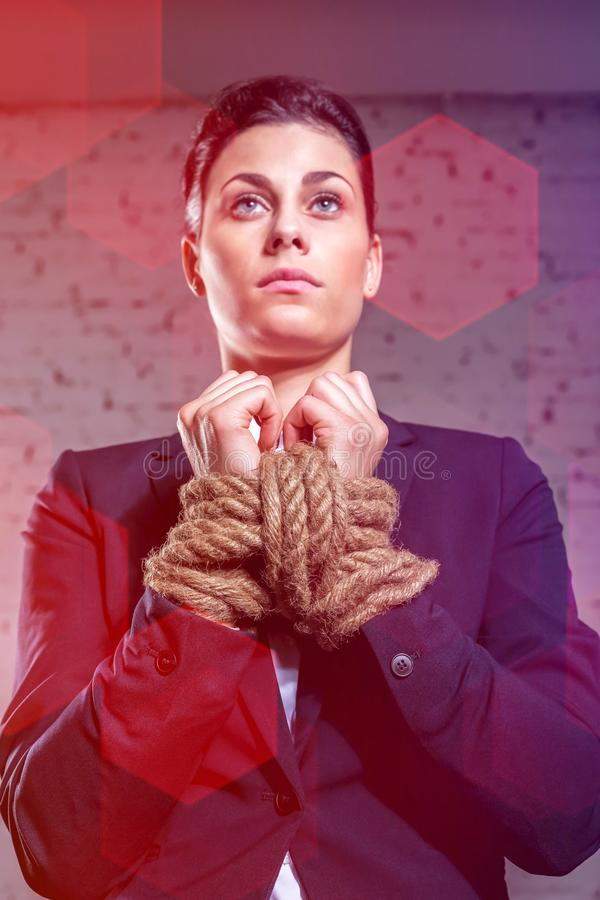 Businesswoman standing with tied hands against wall at office. Young businesswoman standing with tied hands against wall at office royalty free stock images