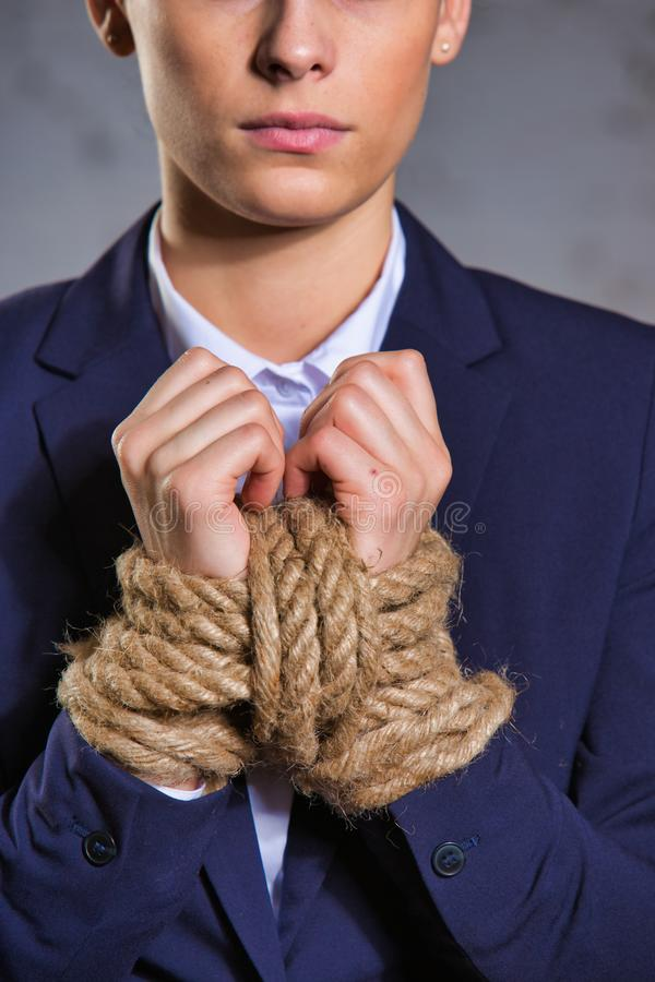 Portrait of young businesswoman standing with tied hands at office. Young businesswoman standing with tied hands at office stock photography