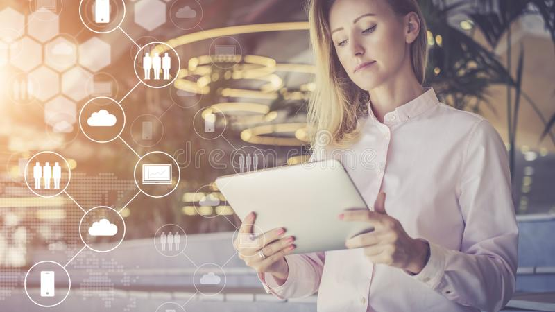 Young businesswoman stands and uses digital.In foreground are virtual icons with clouds, people, digital gadgets. royalty free stock photo