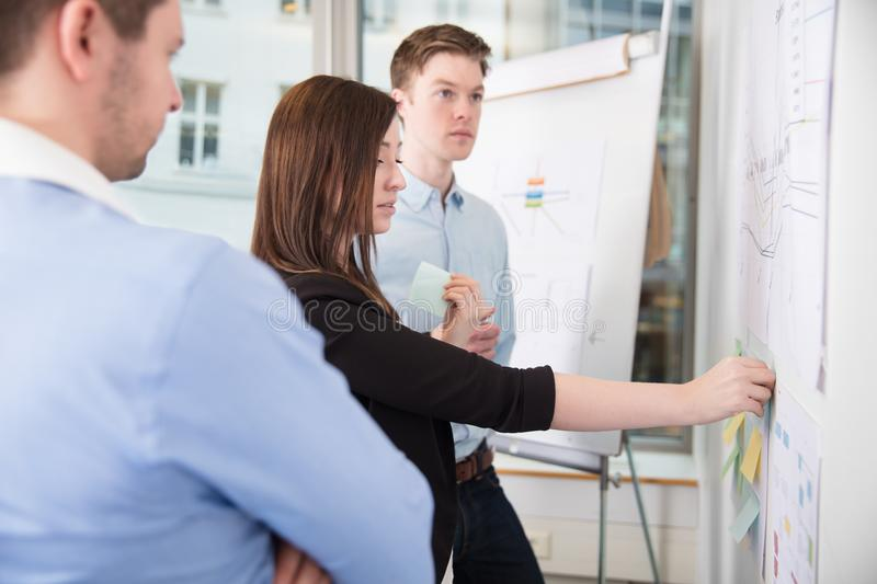 Businesswoman Sticking Notes While Standing By Male Colleagues stock photos