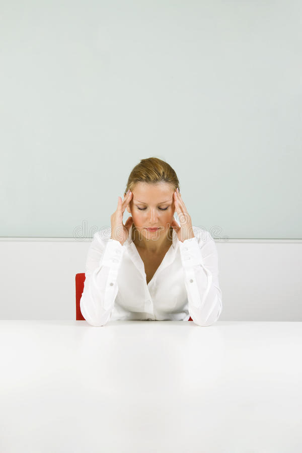 Young businesswoman in stress. Young blond businesswoman in stress, with headache royalty free stock images