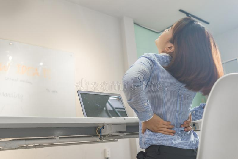 Young businesswoman suffering from back pain in office royalty free stock photo