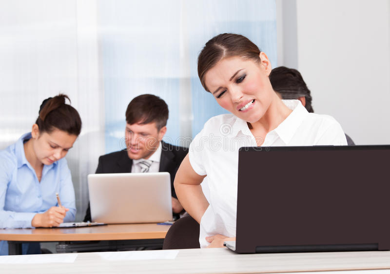 Young businesswoman suffering from back pain stock photos