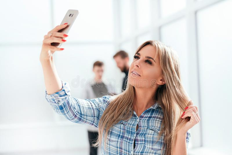 Young businesswoman takes a selfie standing in the office stock photography