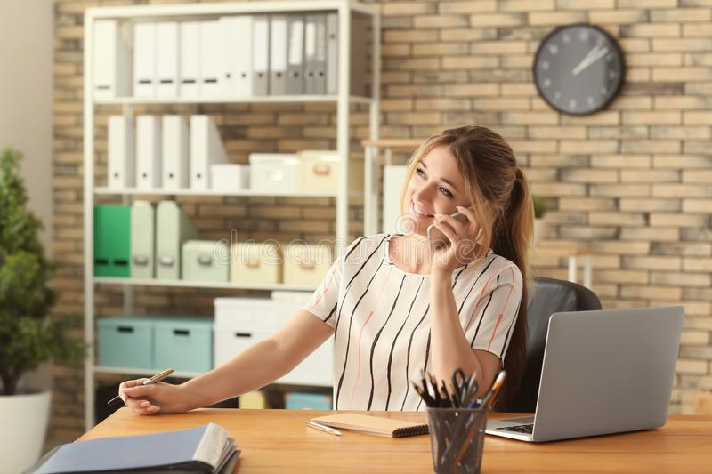 Young businesswoman talking on mobile phone in office stock photos