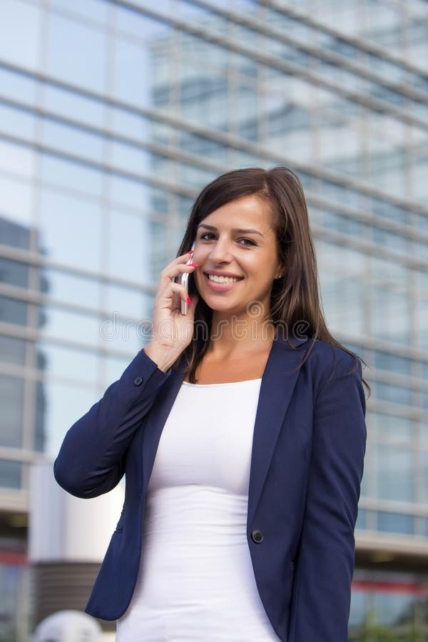 Young businesswoman talking over the mobile phone in fron of off. Portrait of young businesswoman talking over the mobile phone in fron of office building royalty free stock photo