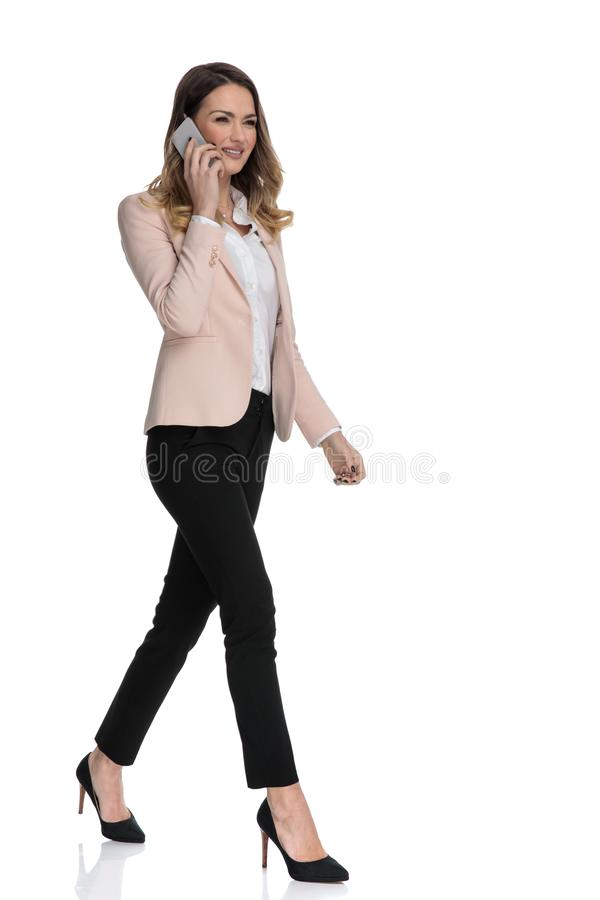 Young businesswoman talking on the phone steps to side royalty free stock image