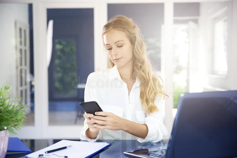 Young businesswoman text messaging in the office royalty free stock image
