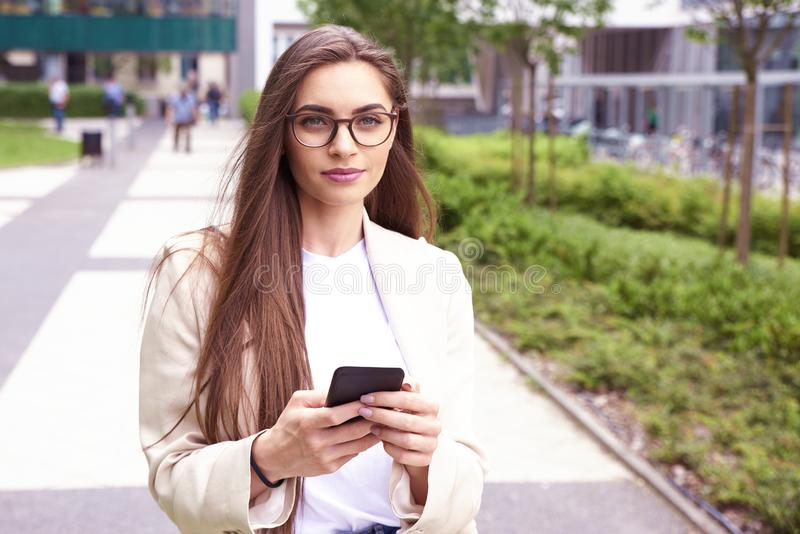 Young businesswoman text messaging while walking on the street in the city stock photography