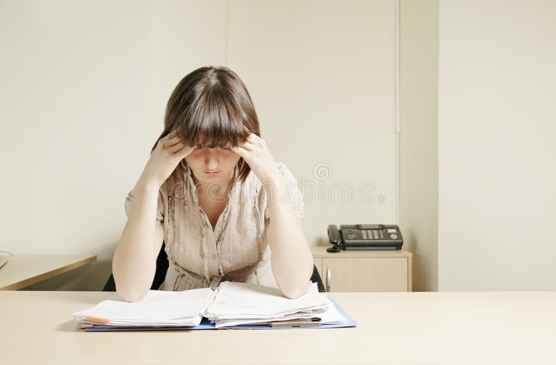 Young Businesswoman Thinking Over Papers Royalty Free Stock Image
