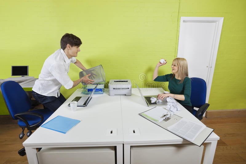 Young businesswoman throwing paper ball at male colleague holding waste bin stock photos