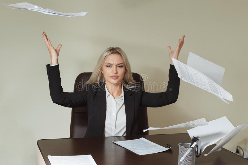 Young businesswoman throwing some paper sheets royalty free stock photo