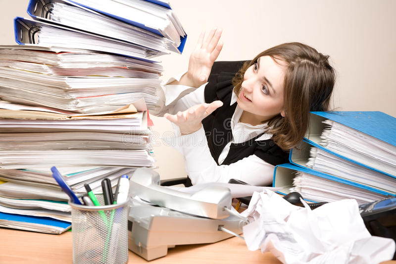 Young businesswoman with tons of documents stock images
