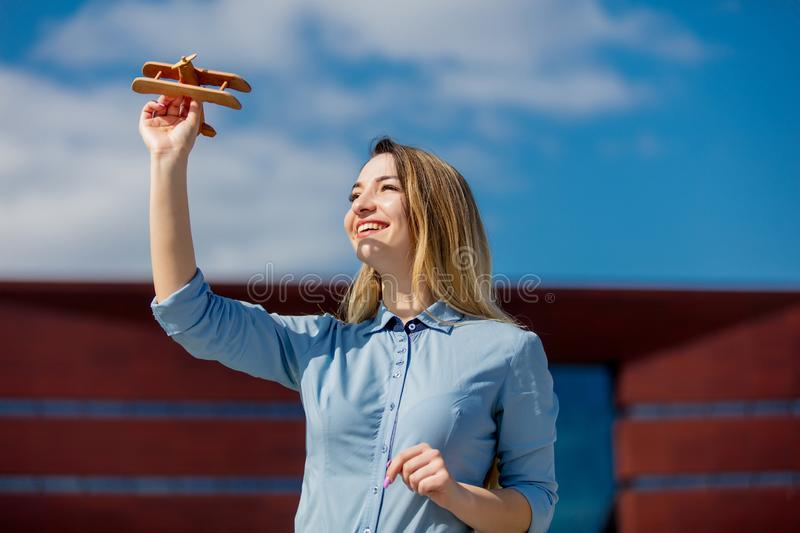 Young businesswoman with toy wooden plane stock image