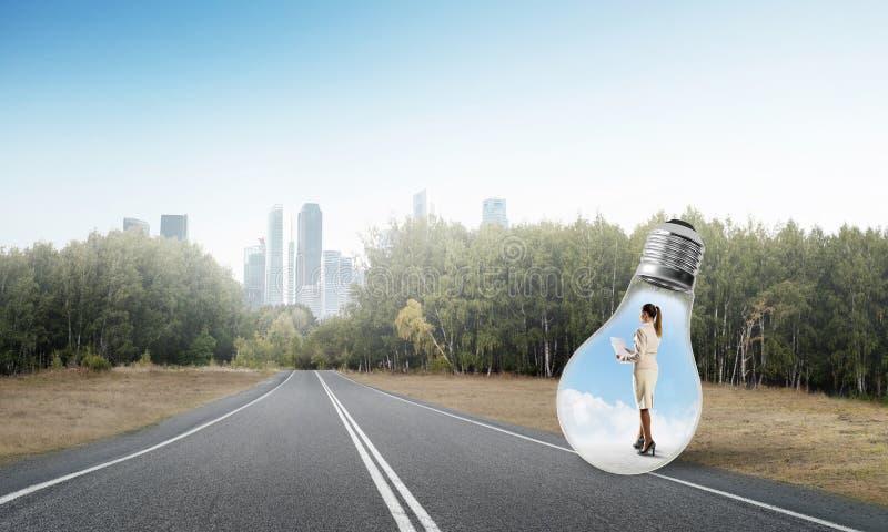 Businesswoman inside light bulb stock photo