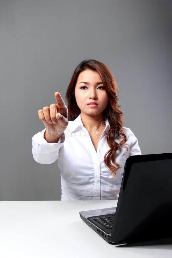 Young businesswoman typing on virtual screen beside a laptop. A portrait of a young businesswoman typing on virtual screen beside a laptop stock photography