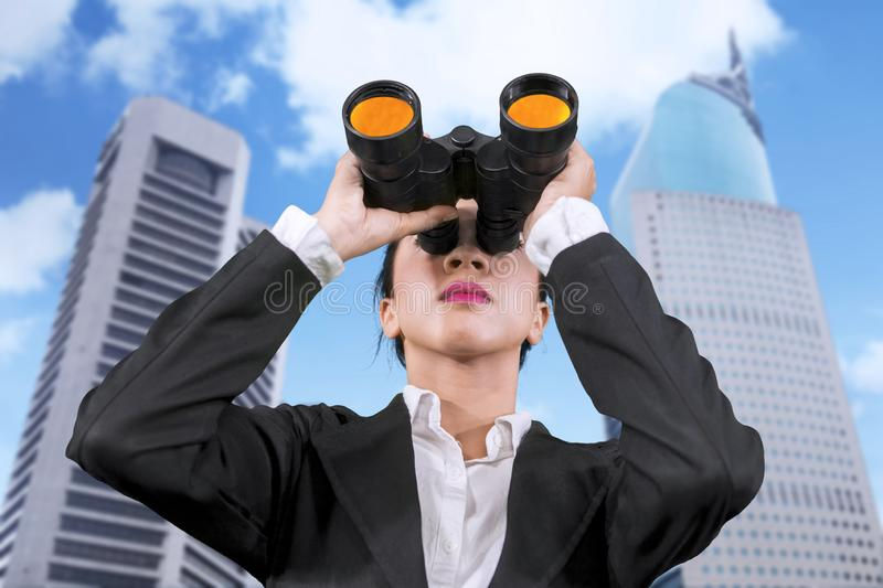 Young businesswoman using binoculars at outdoors stock image
