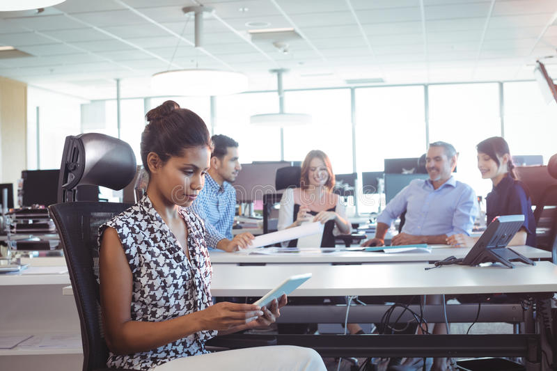 Young businesswoman using digital tablet while colleagues discussing in office. Young businesswoman using digital tablet while colleagues discussing at desk in stock image