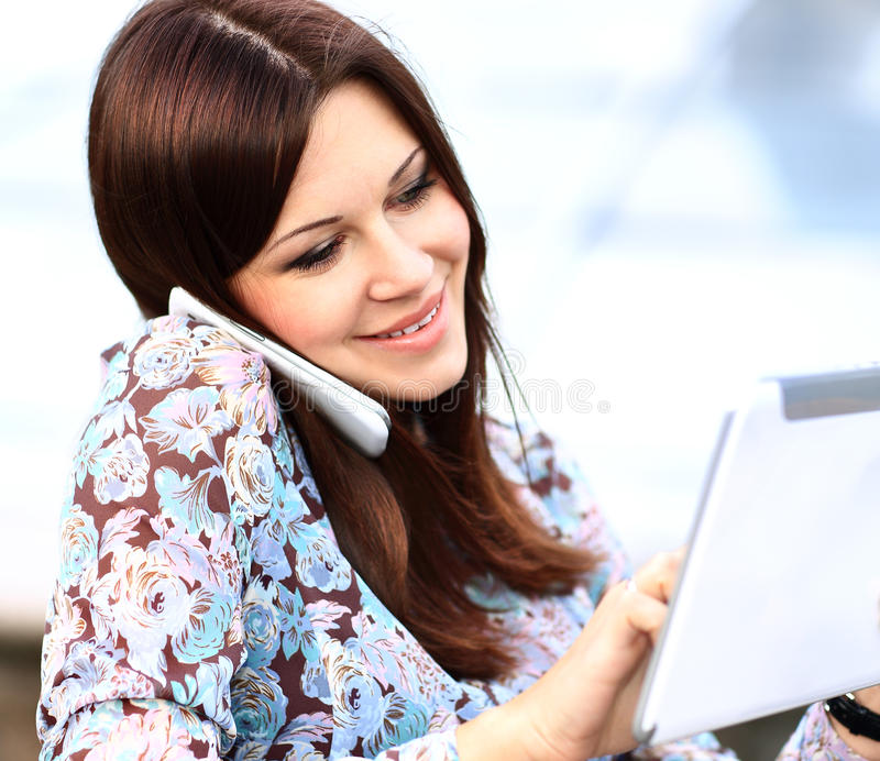 Young businesswoman using digital tablet and mobile phone. Over building background royalty free stock photos
