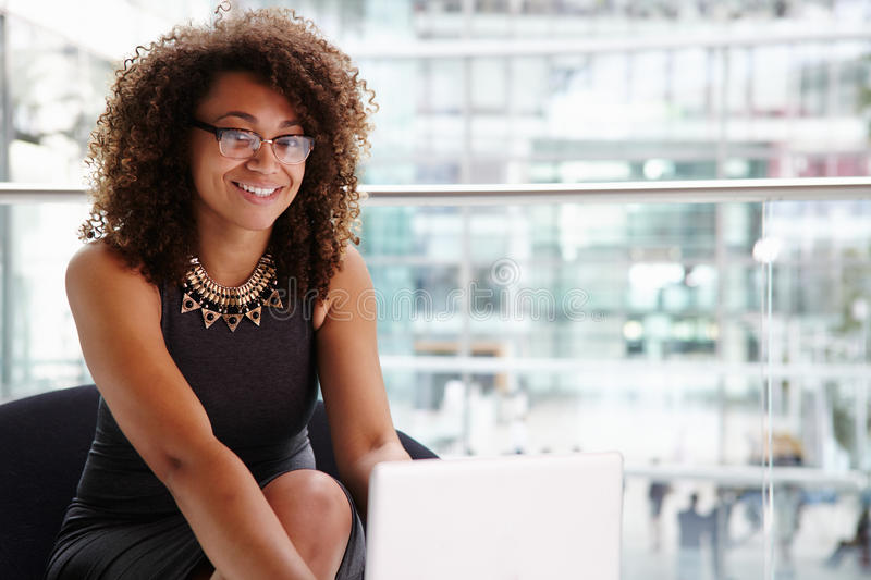 Young businesswoman using laptop computer, looking to camera stock photo