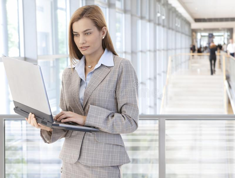 Download Businesswoman Using Laptop In Office Lobby Stock Image - Image: 29951963