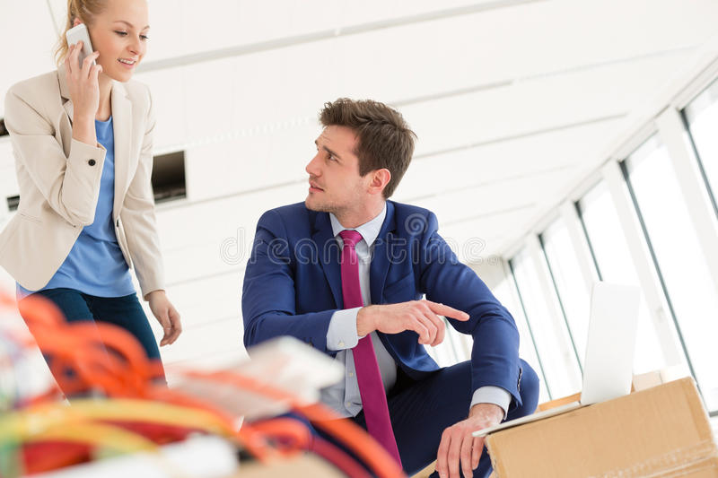 Young businesswoman using mobile phone while male colleague pointing towards laptop in new office.  stock images