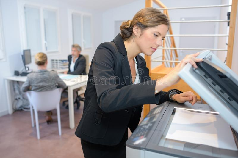 Young businesswoman using photocopy machine in office royalty free stock images