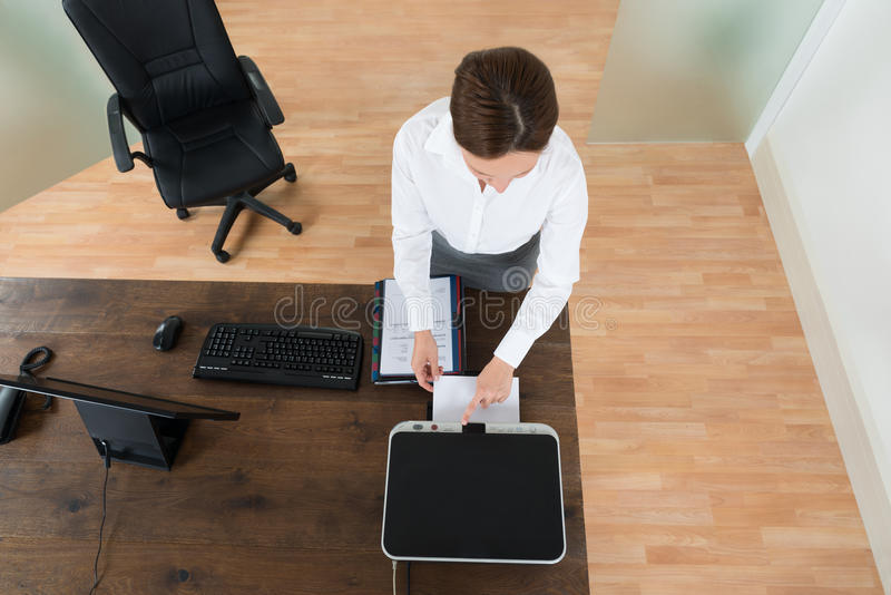 Young Businesswoman Using Printer In Office. High Angle View Of Young Businesswoman Using Printer At Desk In Office royalty free stock photo