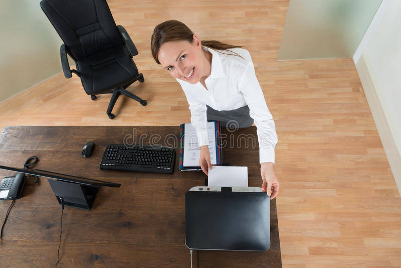 Young Businesswoman Using Printer In Office. High Angle View Of Young Businesswoman Using Printer At Desk In Office stock photo